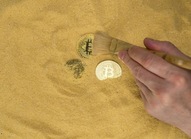 Um arqueólogo com um pincel limpa a moeda bitcoin na areia dourada encontrando criptomoeda