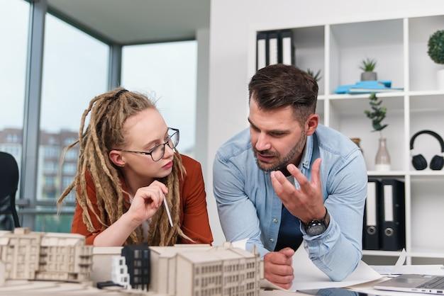 Um arquiteto e uma designer estão discutindo um projeto conjunto para um futuro complexo residencial