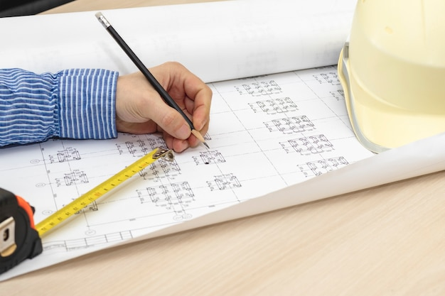 Um arquiteto está trabalhando com um projeto. fazendo alterações nos desenhos de construção. desenvolvimento de um projeto de construção.