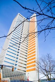 Um arranha-céu alto meio azul e meio laranja no inverno em um céu azul claro