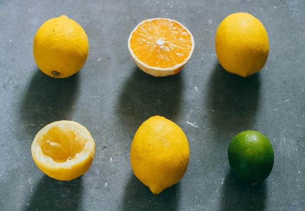 Um arranjo de frutas cítricas, limões, laranja e limão sobre um fundo cinza.
