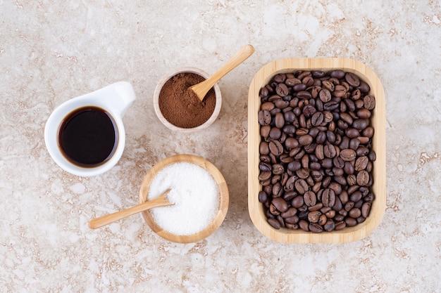 Um arranjo de xícara de café, açúcar, pó de café moído e uma pilha de grãos de café em uma bandeja de madeira