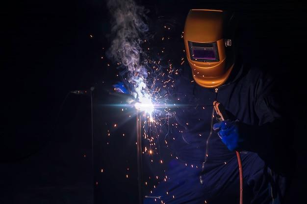 Um artesão está soldando com aço da peça de trabalho.