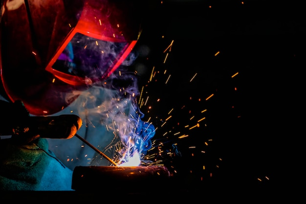 Um artesão está soldando com aço da peça.
