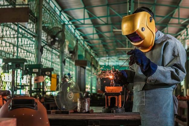 Um artesão está soldando com aço de peça de trabalho.
