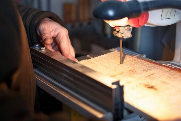 Um artesão que corta uma prancha de madeira com serra de fita