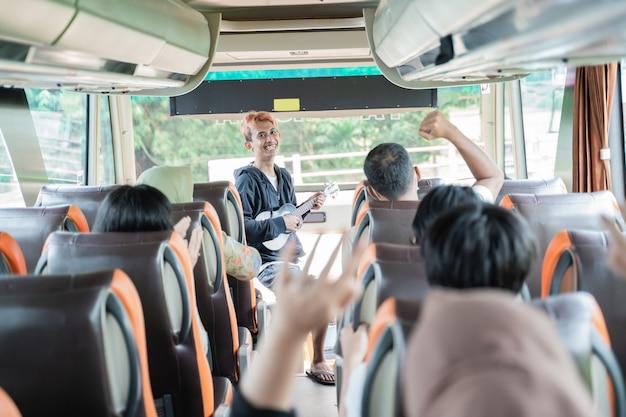 Um artista cantava alegremente enquanto usava um instrumento de ukulele e os passageiros do ônibus batiam palmas no caminho