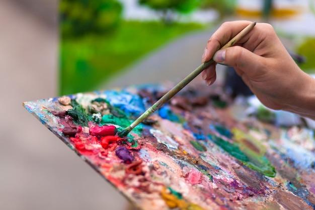 Um artista de close-up pinta em uma tela uma paisagem urbana de um dique de verão com atrações de tintas a óleo