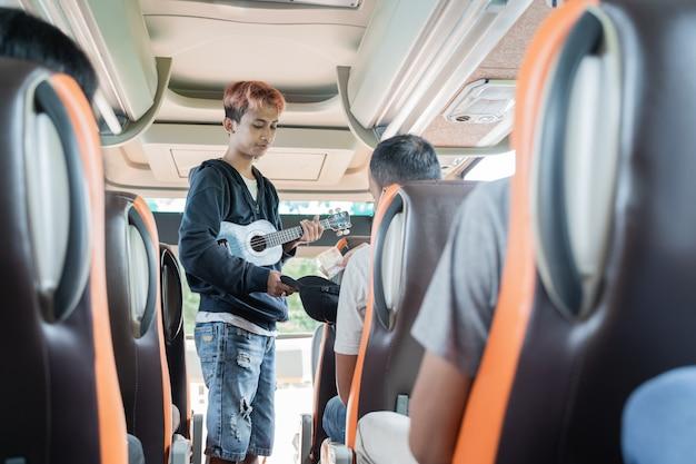Um artista de rua usando um instrumento de ukulele e um chapéu pedindo dinheiro aos passageiros do ônibus durante uma viagem