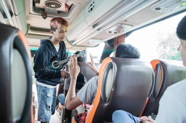 Um artista de rua usando um ukulele pede dinheiro aos passageiros enquanto estão no ônibus