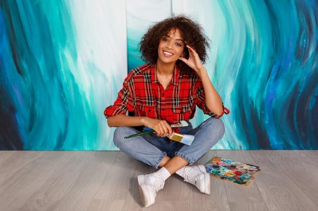 Um artista de sorriso novo da mulher negra no estúdio que guardara uma escova. aluno inspirado sentado sobre suas obras de arte.