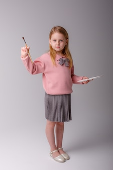Um artista infantil segura um pincel e uma paleta em um espaço cinza