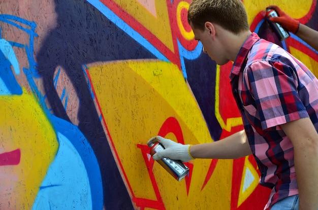 Um artista novo dos grafittis do red-haired pinta um grafitti novo na parede.