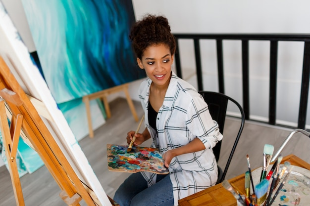 Um artista pensativo novo da mulher negra no estúdio que guardara uma escova. aluno inspirado sentado sobre suas obras de arte.