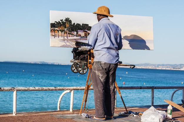 Um artista pinta a óleo na costa inglesa em nice, frança