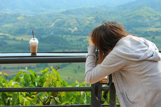 Um asiático que toma uma foto do café congelado no copo plástico com backgound natural da vista.