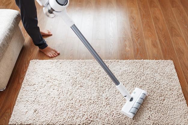 Um aspirador de pó sem fio limpa o carpete da sala com a parte inferior das pernas. tecnologias modernas para limpar a casa. escova turbo
