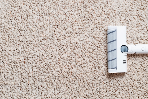 Um aspirador de pó sem fio limpa o carpete da sala com a parte inferior das pernas