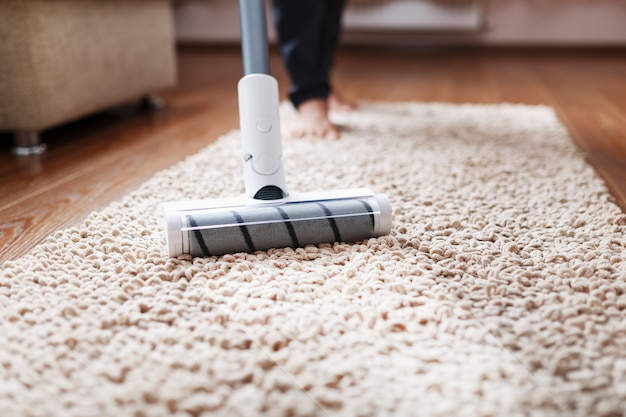 Um aspirador de pó sem fio limpa o carpete da sala com a parte inferior das pernas.