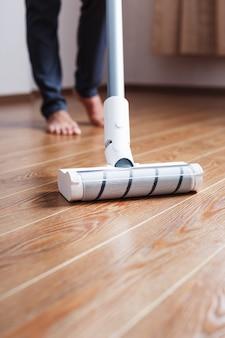 Um aspirador sem fio limpa o parquete da sala com a parte inferior das pernas.