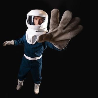 Um astronauta sem gravidade estende a mão. o herói da história de ficção científica é um pioneiro da exploração espacial. um jovem em um traje espacial, distorções de perspectiva
