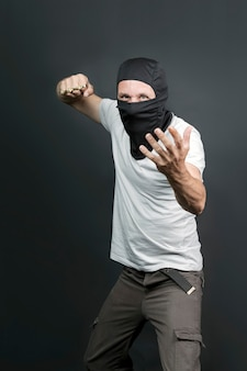 Um ataque ofensivo com soco inglês. soco inglês de metal na mão de um homem caucasiano de máscara preta. armas proibidas em uma luta, criminoso. homem americano mostrando o punho com soco inglês. fechar-se