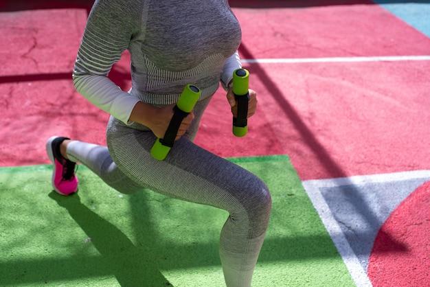 Um atleta com um agasalho cinza fazendo estocadas com halteres no parquinho