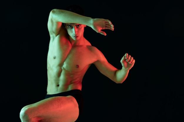 Um atleta com um torso inflado levantou a perna em um fundo preto e fez gestos