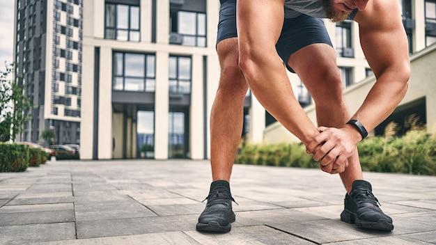 Um atleta de barba com relógio de tênis e shorts inclina-se para os pés com o corpo e as mãos cruzadas na fechadura