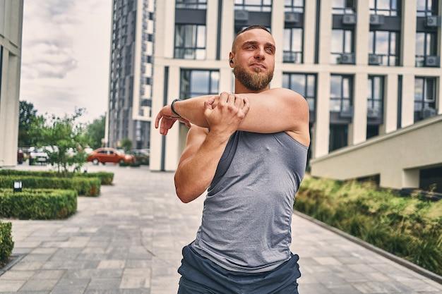 Um atleta de barba comprida com fone de ouvido sem fio na área do escritório massageia os braços e ombros à tarde