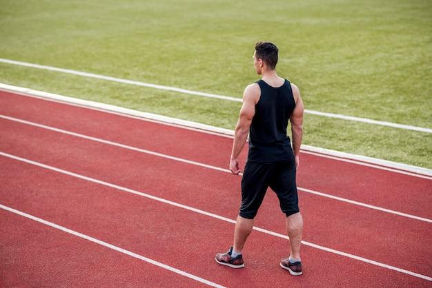 Um atleta do sexo masculino em pé na pista de rack vermelho no estádio