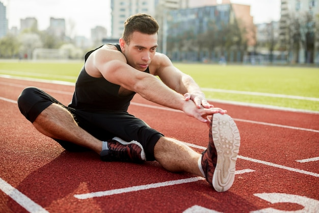 Um atleta masculino, estendendo-se na pista de corrida