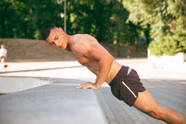 Um atleta masculino musculoso fazendo exercícios no parque. ginástica, treino, flexibilidade de treino de fitness. cidade de verão em dia ensolarado estilo de vida ativo e saudável, juventude, musculação.
