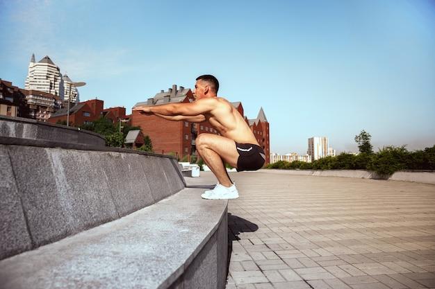 Um atleta masculino musculoso fazendo exercícios no parque. ginástica, treino, flexibilidade de treino de fitness. cidade de verão em um dia ensolarado no campo de fundo. estilo de vida ativo e saudável, juventude, musculação.
