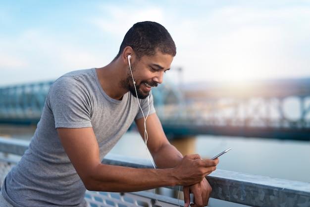 Um atleta usando um smartphone em um intervalo de treinamento para receber mensagens de texto