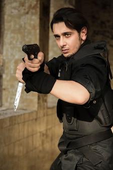 Um ator realizando cena policial com uma arma