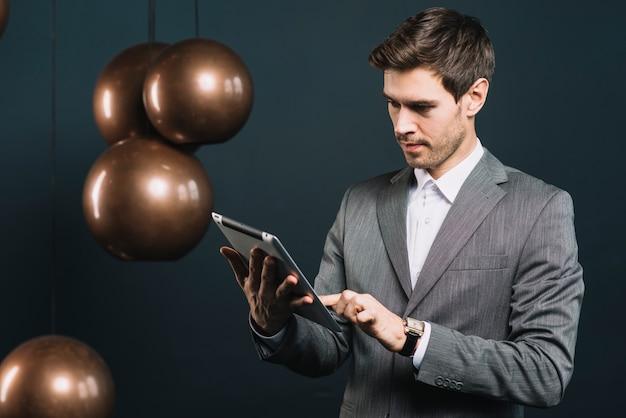 Um, atraente, homem jovem, usando, tablete digital, com, modernos, metal, pingente