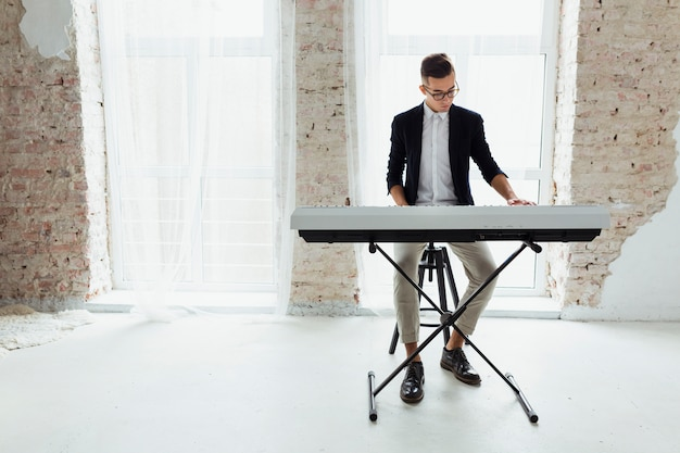 Um atraente jovem tocando piano sentado perto da janela com cortina branca