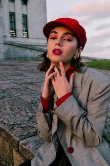 Um, atraente, mulher jovem, toque, dela, queixo, olhando câmera