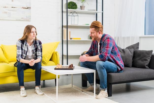 Um, atraente, par jovem, olhando um ao outro, com, tabuleiro xadrez, ligado, tabela