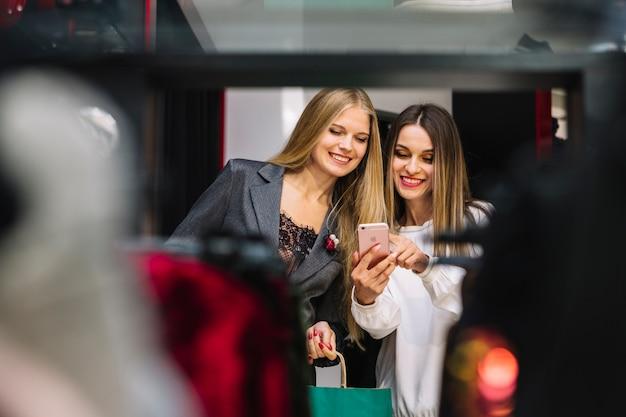 Um, atraente, sorrindo, mulheres jovens, olhar, telefone móvel