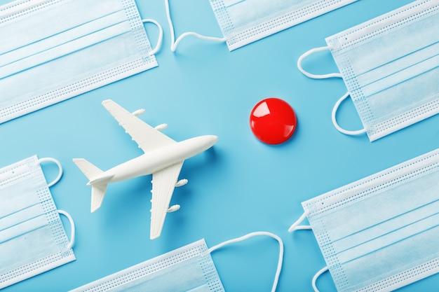 Um avião branco de brinquedo e máscaras de proteção em uma superfície azul com um ponto vermelho como destino