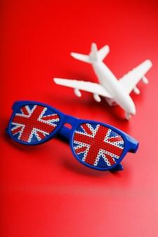 Um avião de passageiros branco voa em óculos de sol com a bandeira do reino unido.