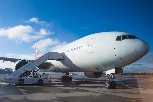 Um avião de passageiros de corpo largo estacionou no aeroporto com uma rampa na entrada, contra um céu azul