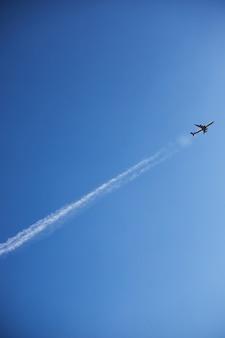 Um avião em um céu claro decola deixando uma linha
