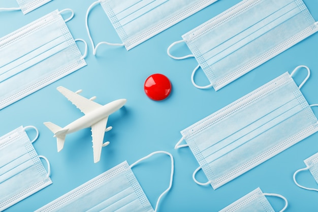 Um avião em uma superfície azul cercada por máscaras médicas com um ponto vermelho de destino