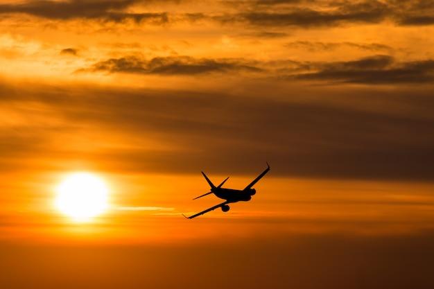 Um avião voando em direção a um belo pôr do sol