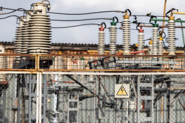 Um aviso de aviso dos perigos da alta tensão elétrica paira sobre a cerca de malha que circunda a subestação de linha de energia.