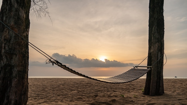 Um balanço de madeira ou berço na praia com belas nuvens e céu.