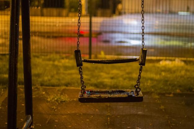 Um balanço vazio no parque na noite chuvosa